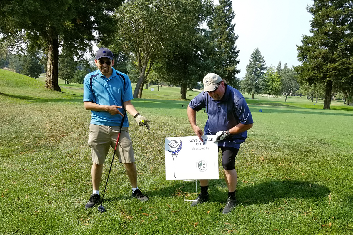 Two golf participants posing on course