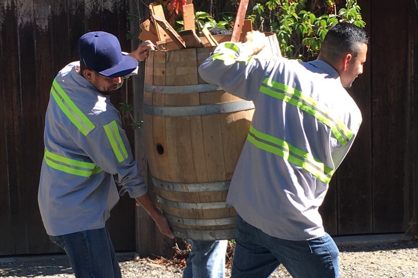 Event supplies being carried in wine barrels by two workers